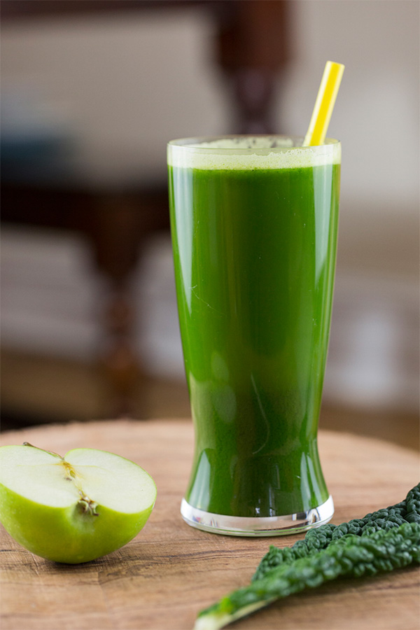 A photograph of a green smoothie in a glass with a green apple and kale